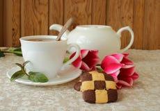 Aún-vida con una taza de té negro, de galletas y de tulipanes Imagenes de archivo