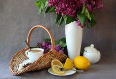 Aún-vida con una taza de té y una rama de la lila Imagenes de archivo