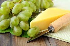 Aún-vida con uvas verdes y un pedazo de queso Fotos de archivo