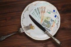 Aún vida conceptual con el dinero en la placa Fotos de archivo