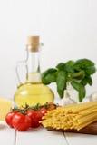 Aún vida culinaria con el bucatini seco de las pastas, los tomates frescos y la albahaca, botella de aceite en fondo ligero Imagenes de archivo