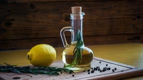 Aún-vida de la botella del aceite de oliva sobre fondo oscuro Foto de archivo libre de regalías
