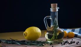 Aún-vida de la botella del aceite de oliva sobre fondo oscuro Imagen de archivo
