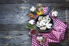 Aún-vida de la cocina con las setas en una sartén negra del arrabio, nuevas patatas, hierbas del jardín, cebollas y un ajo en de  Fotos de archivo