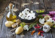 Aún-vida de la cocina con las setas en una sartén negra del arrabio, nuevas patatas, hierbas del jardín, cebollas y un ajo en de  Imágenes de archivo libres de regalías