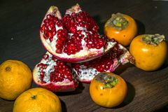 Aún-vida de la cocina Frutas maduras sanas de la granada, del mandarín y del caqui en una tabla del marrón oscuro Imagen de archivo