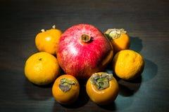 Aún-vida de la cocina Frutas maduras sanas de la granada, del mandarín y del caqui en una tabla del marrón oscuro Foto de archivo