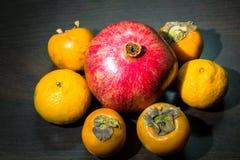 Aún-vida de la cocina Frutas maduras sanas de la granada, del mandarín y del caqui en una tabla del marrón oscuro Imágenes de archivo libres de regalías