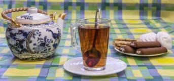 Aún-vida de la mañana con una taza de té, un té y dulces de cristal Imagen de archivo