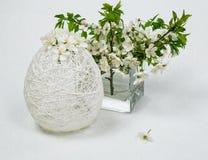 Aún-vida de la primavera en una cereza floreciente en un florero y un huevo de Pascua de cristal Imágenes de archivo libres de regalías