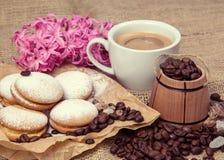 Aún-vida de la primavera de una taza de café con la leche, galletas, una flor Imagen de archivo libre de regalías