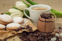 Aún-vida de la primavera de una taza de café con la leche, galletas, un ramo de tulipanes blancos Foto de archivo libre de regalías