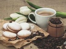 Aún-vida de la primavera de una taza de café con la leche, galletas, un ramo de tulipanes blancos Imágenes de archivo libres de regalías