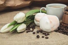 Aún-vida de la primavera de una taza de café con la leche, melcocha, un ramo de tulipanes blancos Foto de archivo
