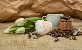 Aún-vida de la primavera de una taza de café con la leche, melcocha, un ramo de tulipanes blancos Foto de archivo libre de regalías
