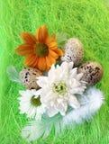 Aún-vida de Pascua con las flores, huevos, plumas en una fibra del sisal Fotografía de archivo