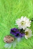Aún-vida de Pascua con las flores, huevos, plumas en una fibra del sisal Foto de archivo