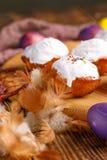 Aún-vida de Pascua con las magdalenas en el esmalte blanco e inusualmente coloreados los huevos en un fondo de madera Fotografía de archivo