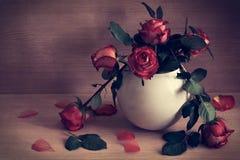 Aún-vida de rosas rojas en un florero blanco Fotografía de archivo libre de regalías