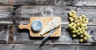 Aún-vida del brie francés, del queso de cabra y de la uva blanca Fotos de archivo libres de regalías