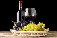 Aún-vida del lagar Variedades de uvas con la copa y la botella de vino en fondo negro Foto de archivo