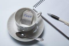 Aún-vida del negocio con con una taza de té y de bolsitas de té Fotografía de archivo
