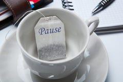 Aún-vida del negocio con con una taza de té y de bolsitas de té Foto de archivo
