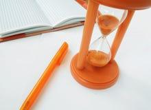 Aún-vida del negocio con un reloj de arena, un cuaderno y una pluma Imagen de archivo libre de regalías
