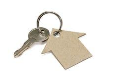 Aún-vida del negocio con una llave y casa en el fondo blanco Imagen de archivo libre de regalías