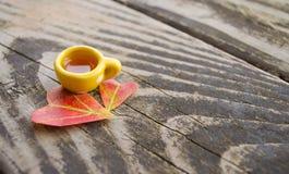 Aún-vida del otoño Una taza de bebida caliente y dos hojas en la forma de corazones en un fondo de madera gris Foto de archivo