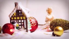 Aún-vida del ` s del Año Nuevo con la figura de una casa, de juguetes del ángel, rojos y amarillos del árbol de navidad y con des almacen de video