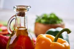 Aún vida deliciosa con aceite de oliva de oro en el tarro de cristal entre verduras frescas, primer, foco selectivo Fotografía de archivo libre de regalías