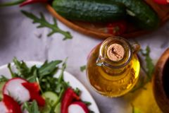 Aún vida deliciosa con aceite de oliva de oro en el tarro de cristal entre verduras frescas, primer, foco selectivo Foto de archivo libre de regalías