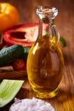 Aún vida deliciosa con aceite de oliva de oro en el tarro de cristal entre verduras frescas, primer, foco selectivo Fotos de archivo libres de regalías