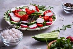 Aún vida deliciosa con aceite de oliva de oro en el tarro de cristal entre verduras frescas, primer, foco selectivo Foto de archivo
