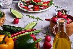 Aún vida deliciosa con aceite de oliva de oro en el tarro de cristal entre verduras frescas, primer, foco selectivo Fotografía de archivo
