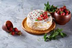 Aún vida deliciosa con la tarta de la fresa cubierta con crema agria, la fresa y la menta azotadas en el fondo blanco Imagen de archivo libre de regalías