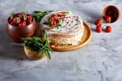 Aún vida deliciosa con la tarta de la fresa cubierta con crema agria, la fresa y la menta azotadas en el fondo blanco Imagenes de archivo