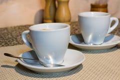 Aún-vida, dos tazas de café, placas blancas de la porción, pequeño metal s Imagen de archivo
