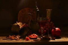 Aún-vida en estilo del este con uvas, una granada y un jarro Foto de archivo