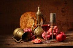 Aún-vida en estilo del este con uvas, una granada y un jarro Fotos de archivo