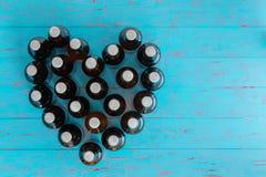 Aún vida en forma de corazón de las botellas de cerveza capsuladas Imagenes de archivo