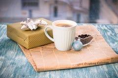 Aún vida festiva con la caja, taza, florero, bola azul, periódico Imagen de archivo libre de regalías