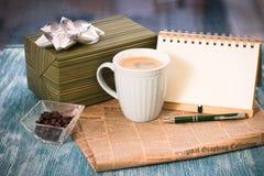 Aún vida festiva con la caja, taza, florero, periódico, cuaderno Foto de archivo