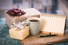 Aún-vida festiva con los presentes, una taza, un cuaderno del RA Imágenes de archivo libres de regalías