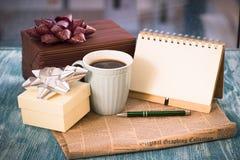 Aún-vida festiva con los presentes, una taza, un cuaderno, pluma del RA Fotografía de archivo libre de regalías