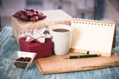 Aún-vida festiva con los presentes, una taza, un florero, un cuaderno del RA Fotografía de archivo