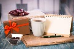 Aún-vida festiva con los presentes, una taza, un florero, un cuaderno del RA Fotografía de archivo libre de regalías