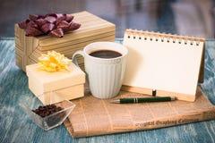 Aún-vida festiva con los presentes, una taza, un florero, un cuaderno del RA Foto de archivo