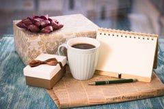 Aún vida festiva con los regalos, una taza, un cuaderno Fotos de archivo